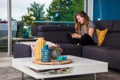 Jovem mulher que texting e que refrigera no sofá imagem de stock royalty free