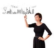 Jovem mulher que tira cidades e marcos famosos no whiteboard fotografia de stock royalty free