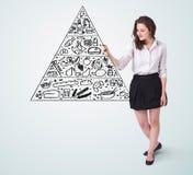 Jovem mulher que tira uma pirâmide de alimento no whiteboard Imagens de Stock