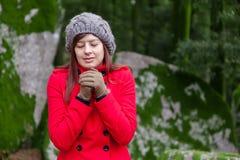 Jovem mulher que tirita com frio em uma floresta Fotos de Stock