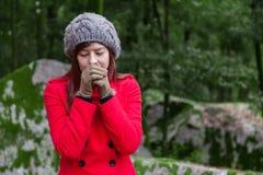Jovem mulher que tirita com frio em uma floresta Imagens de Stock
