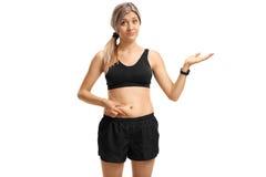 Jovem mulher que toca em sua barriga gorda e que gesticula com mão foto de stock