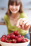Jovem mulher que toma Cherry From Wooden Bowl Imagem de Stock
