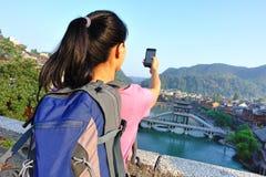 Jovem mulher que toma a foto com o telefone esperto no fenghuang t antigo fotografia de stock royalty free