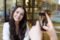 Jovem mulher que toma a foto de seu amigo Imagens de Stock