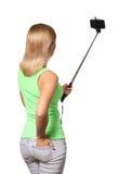 Jovem mulher que toma a foto do selfie com a vara isolada imagem de stock
