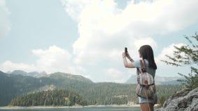 Jovem mulher que toma a foto por Smartphone na frente do lago mountain Menina caucasiano bonita que passa o tempo em um Moutain video estoque