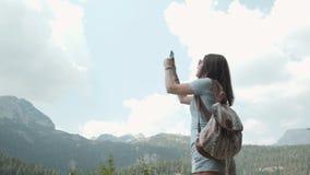 Jovem mulher que toma a foto por Smartphone na frente do lago mountain Menina caucasiano bonita que passa o tempo em um Moutain Foto de Stock Royalty Free