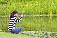 Jovem mulher que toma fotografias Foto de Stock Royalty Free