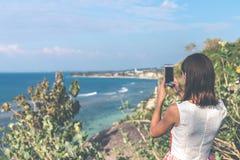 Jovem mulher que toma fotos no penhasco com um fundo bonito do oceano no dia ensolarado Ilha de Bali foto de stock