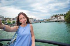 Jovem mulher que toma a fundo do selfie a igreja de Fraumunster e o rio famosos Limmat, Suíça foto de stock royalty free