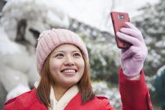 Jovem mulher que toma a imagem com telefone celular na neve Fotografia de Stock