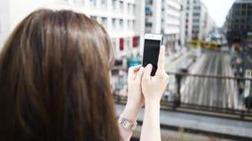Jovem mulher que toma imagens de uma cidade alemão com seu smartphone video estoque