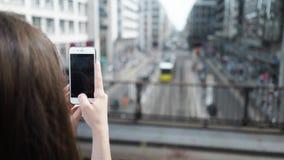 Jovem mulher que toma imagens de uma cidade alemão com seu telefone celular filme