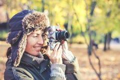 Jovem mulher que toma imagens no parque do outono imagens de stock royalty free