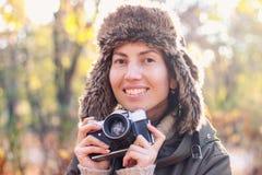 Jovem mulher que toma imagens no parque do outono fotografia de stock royalty free