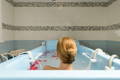 Jovem mulher que toma o banho com leite e as pétalas cor-de-rosa Fotos de Stock Royalty Free