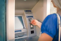 Jovem mulher que toma o dinheiro do ATM fotografia de stock