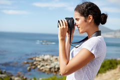 Jovem mulher que toma o pics do oceano fotos de stock