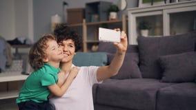 Jovem mulher que toma o selfie com o rapaz pequeno que beija e que abraça usando o smartphone