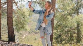 Jovem mulher que toma o selfie com telefone celular fora filme