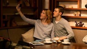 Jovem mulher que toma uma foto com seu telefone celular em um café video estoque