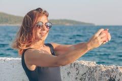 Jovem mulher que toma uma foto usando o smartphone fotografia de stock royalty free