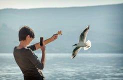 Jovem mulher que toma uma imagem com seu telefone do rebanho das gaivotas fotos de stock
