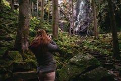 Jovem mulher que toma uma imagem de uma cachoeira na floresta imagem de stock