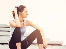 Jovem mulher que toma uma ruptura do exercício fora com telefone celular imagens de stock