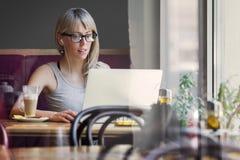 Jovem mulher que trabalha com o computador no café Fotos de Stock Royalty Free