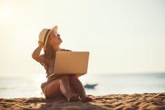 Jovem mulher que trabalha com o port?til na natureza na praia fotos de stock royalty free