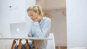 Jovem mulher que trabalha em seu laptop em casa filme