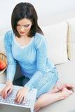 Jovem mulher que trabalha na casa do portátil Imagem de Stock
