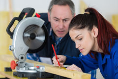 Jovem mulher que trabalha na loja do carpinteiro com professor fotografia de stock