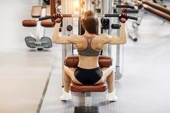 Jovem mulher que trabalha na máquina do pulldown do lat no gym, imagens de stock