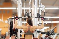 Jovem mulher que trabalha na máquina do pulldown do lat no gym, fotografia de stock royalty free