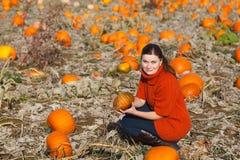 Jovem mulher que trabalha no campo da abóbora Fotografia de Stock Royalty Free