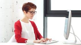 Jovem mulher que trabalha no escrit?rio, sentando-se na mesa, usando o computador e olhando na tela vídeos de arquivo