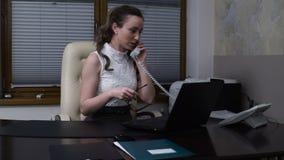 Jovem mulher que trabalha no portátil e que flerta com o noivo no telefone video estoque