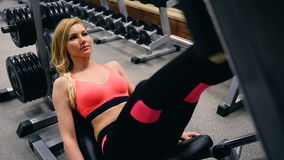 Jovem mulher que trabalha seus quadriláteros na imprensa da máquina no gym Morena latino-americano bonita que exercita em um simu filme