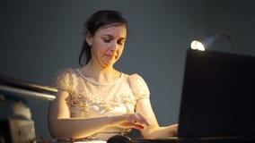 Jovem mulher que trabalha tarde em um escritório com portátil vídeos de arquivo