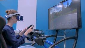 Jovem mulher que usa auriculares da realidade virtual e jogando no simulador da movimentação do carro vídeos de arquivo