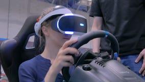 Jovem mulher que usa auriculares da realidade virtual e jogando no simulador da movimentação do carro filme
