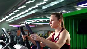 Jovem mulher que usa a escada deslizante ao ter o cardio- exercício no gym video estoque