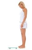 Jovem mulher que usa a escala de banheiro Foto de Stock