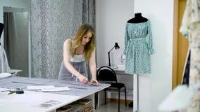 Jovem mulher que usa a fita de medição para cortar a tela para a roupa nova filme