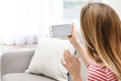 Jovem mulher que usa o bate-papo video no smartphone na sala, close up Espa?o para o projeto foto de stock