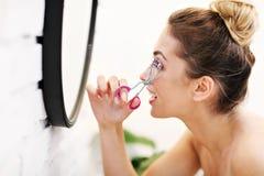 Jovem mulher que usa o encrespador da pestana no banheiro fotografia de stock