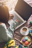 Jovem mulher que usa o portátil na atmosfera home acolhedor fotografia de stock royalty free